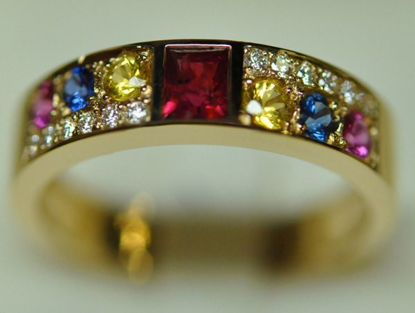 Ruby yellow gold ring in the center and colored sapphires