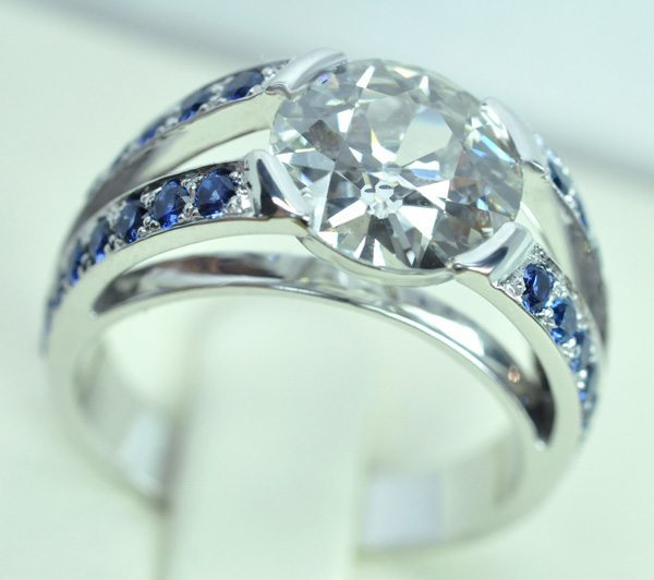 White gold diamond ring. Palmettes set with 4 lines of diamond cut sapphires