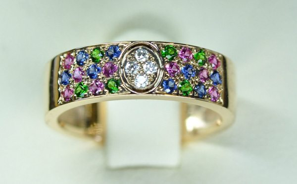 Rose gold ring. Paving of pink / blue sapphires and tsavorite garnets. In the center 4 diamonds