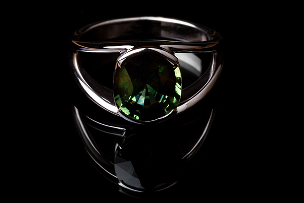 Clean ring. In the center a green sapphire. Palladium-plated white gold setting