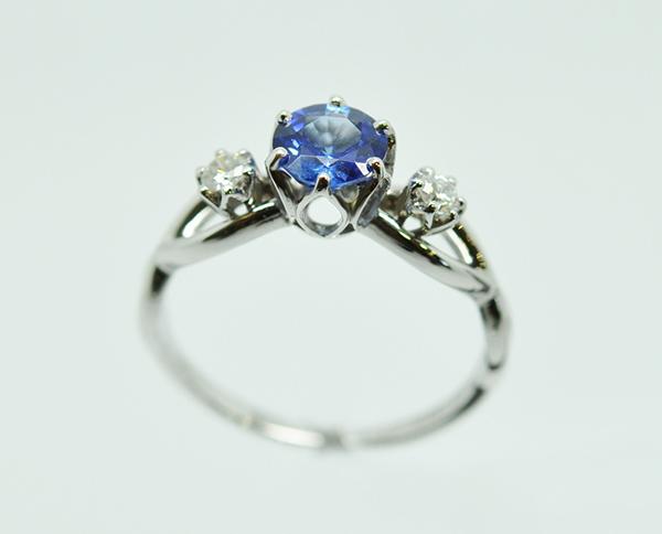 Bague monture or blanc palladié. Au centre un saphir rond serti par 6 griffes. Deux petits diamants sertis entre les courbes de l'anneau.