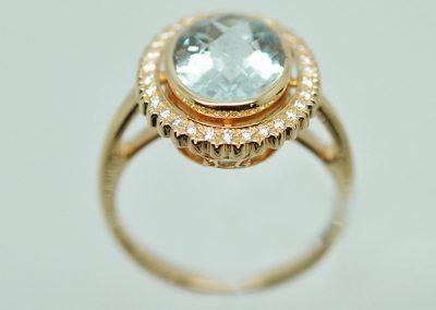 Bague, monture or jaune. Au centre, une Aigue Marine ovale. Entourage de petits diamants serti festonné.