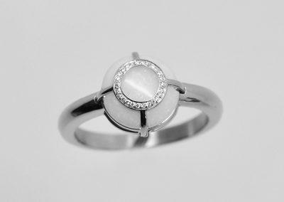 Bague opale blanche. Montage d'un anneau incrusté dans la pierre sertis de diamants.